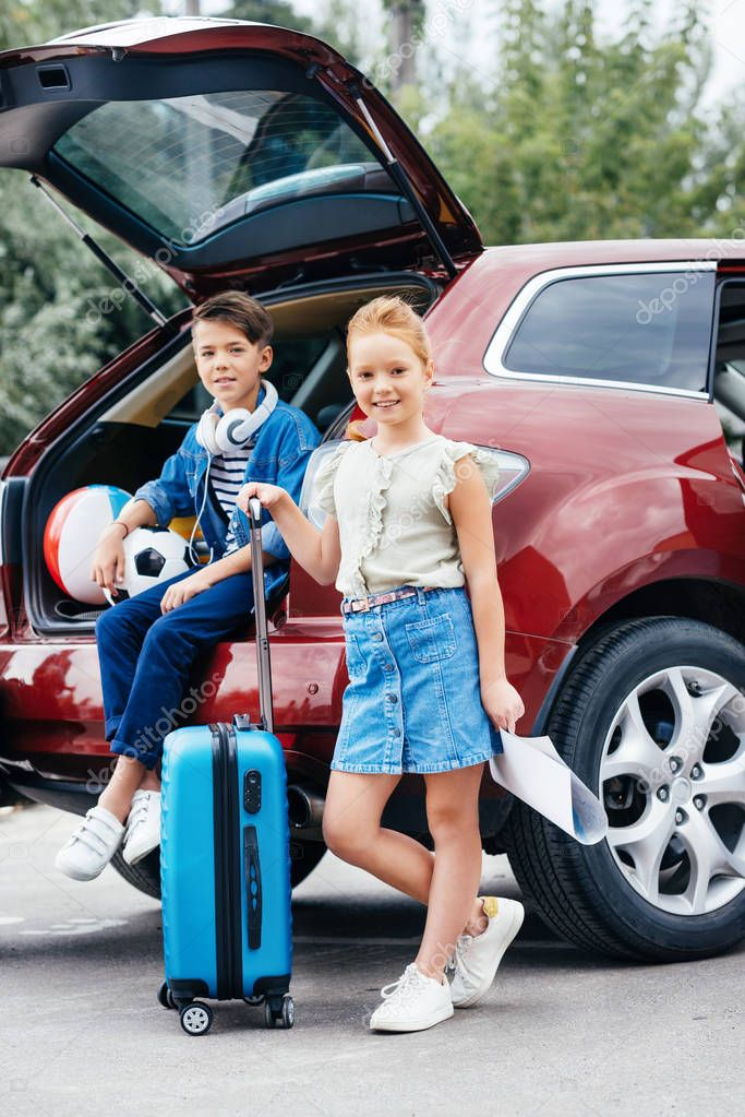 kids with luggage standing next to car
