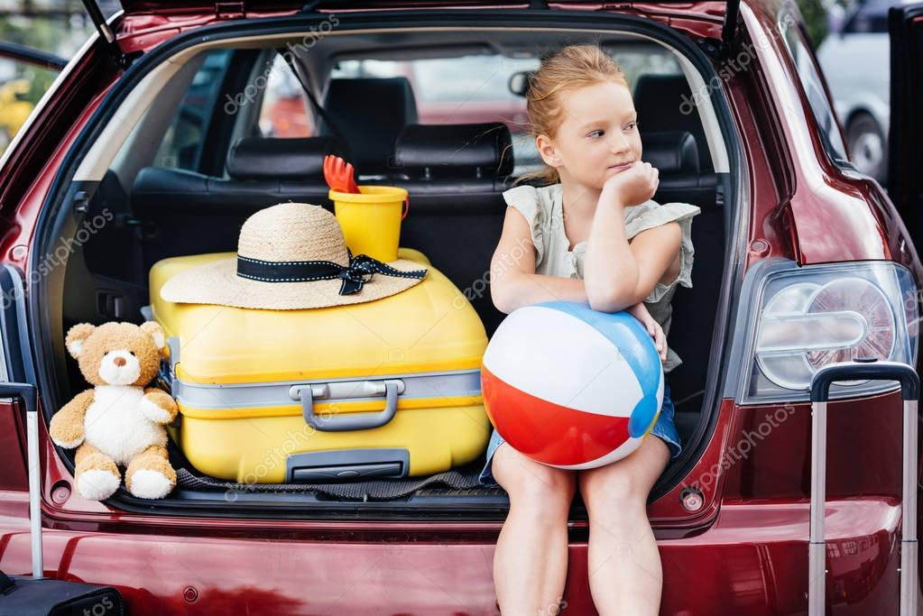 travelling girl sitting in car trunk