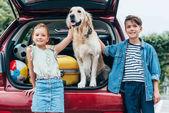 Fotografie Kinder mit Hund im Kofferraum eines Autos