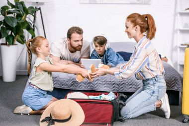 Family packing luggage for trip