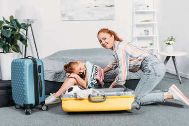 Mother trying to pack clothes into suitcase while adorable daughter sitting in it stock vector