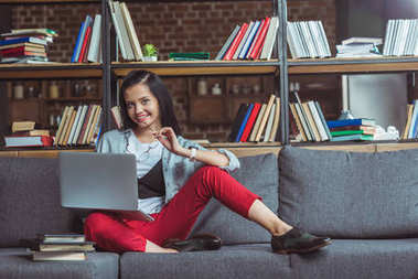 girl studying with laptop and books