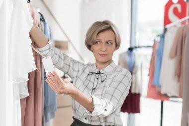 Woman looking at tag on shirt