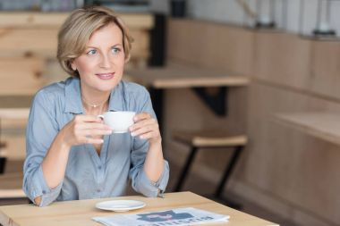 Woman drinking coffee at cafe