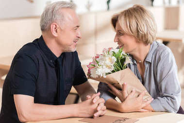 Man presenting flowers to woman