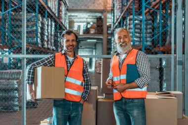 Cheerful male warehouse workers with clipboard and box smiling at camera stock vector