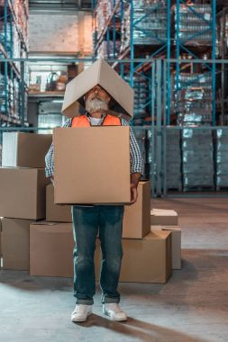 Bearded mature warehouse worker standing with boxes stock vector