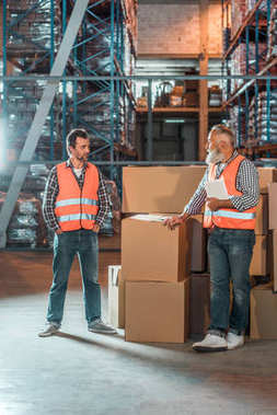 Warehouse workers with digital tablet standing near boxes and looking at each other stock vector