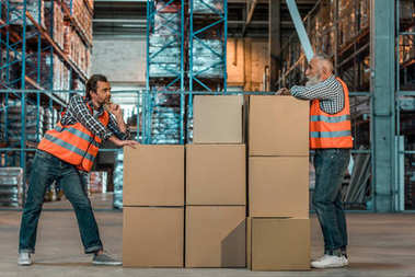 Full length view of two male warehouse workers standing with boxes and looking at each other stock vector