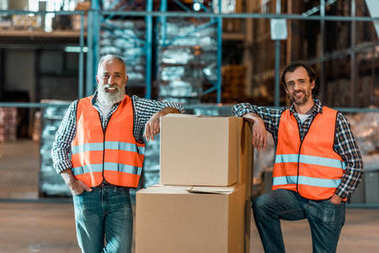 Handsome middle aged warehouse workers standing with boxes and smiling at camera stock vector