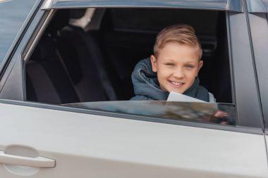 boy with digital tablet in car