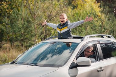 boy standing in car sunroof