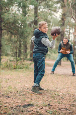 father and son playing with ball in forest