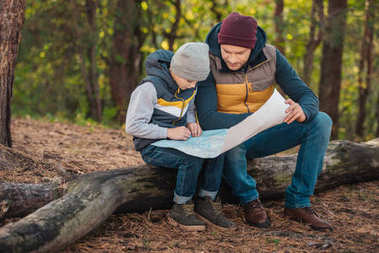 father and son with map in forest