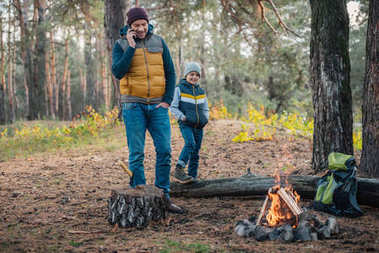 father with smartphone and son in forest