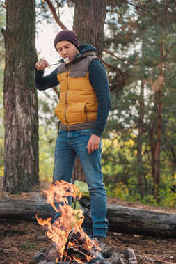 man eating marshmallow in forest
