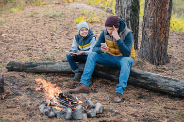 father and son with devices in forest