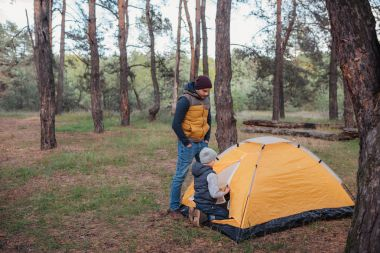 father and son with tent
