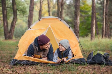 father and son lying in tent