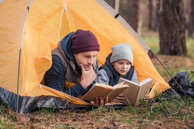 father and son reading books in tent