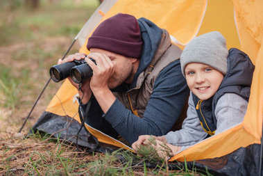 father and son with binoculars in tent