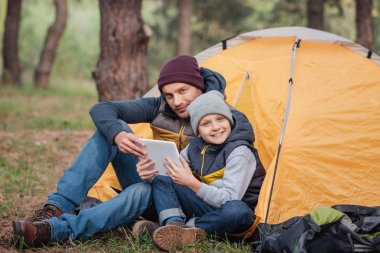 father and son with digital tablet in forest