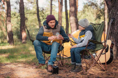 father and son eating in forest