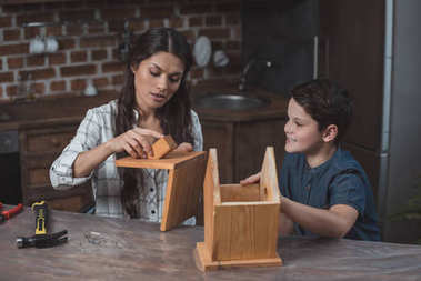 Mother and son workign on birdhouse