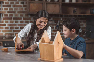Mother and son assembling birdhouse