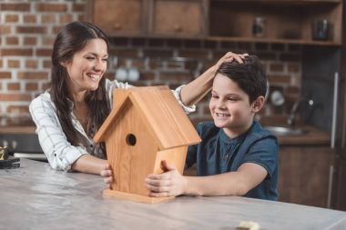 Proud son and mother with birdhouse