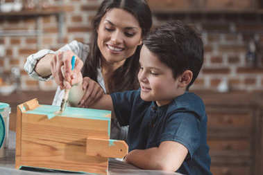 Mother and son painting birdhouse