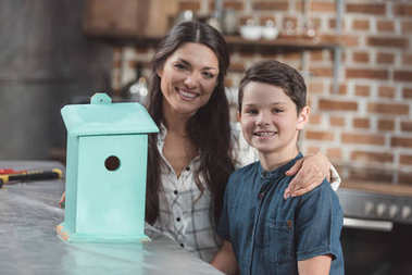 Son and mother with wooden birdhouse