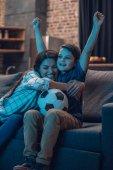 Objímat matku a syna sledovat fotbal