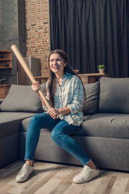 Woman with bat watching baseball on tv