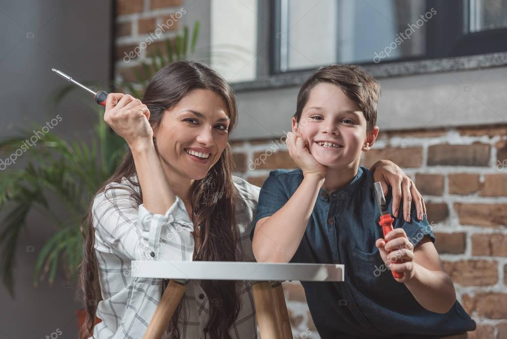Mother and son holding screwdrivers