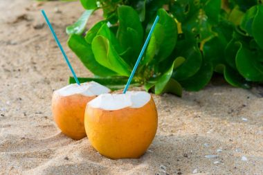 cocktails in coconuts on sand