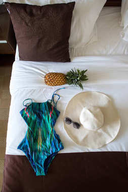 swimsuit with hat and pineapple on bed