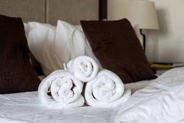 rolled towels on bed