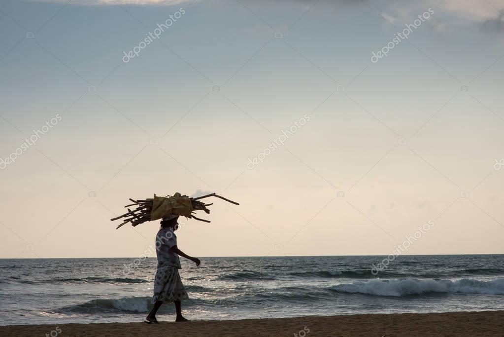 old woman walking by seashore