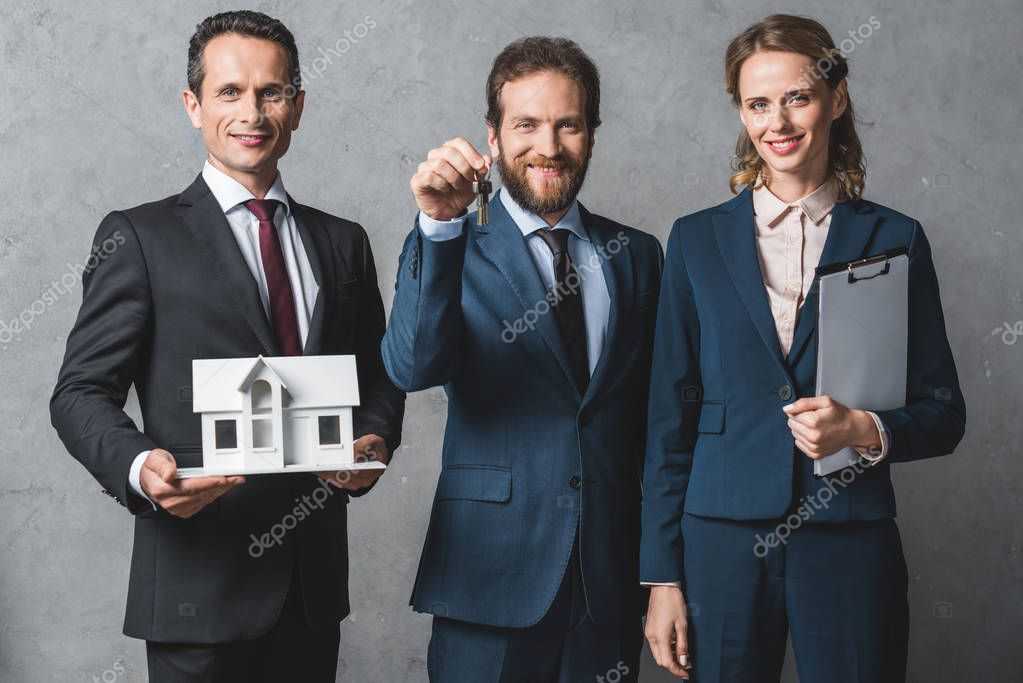 Portrait of smiling business people with house model, keys and folder looking at camera