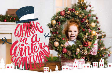 Portrait of happy little girl with christmas wreath, with