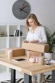Fotografie portrét krásné podnikatel balení výrobků v lepenkových krabicích v domácí kanceláři