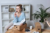 portrait of pensive online shop proprietor with pen and notebook looking away at table at home office