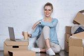 Fotografie usmívající se podnikatel s kávou se jít sedět na podlaze na domácí kancelář