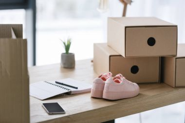 freelance worker workplace with cardboard boxes, notebook and pair of shoes at home office