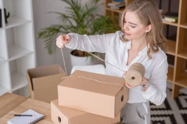 entrepreneur packing customers purchase in cardboard boxes at home office