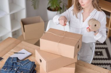 partial view of entrepreneur packing customers purchase in cardboard boxes at home office