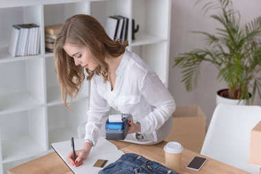 side view of young entrepreneur with credit card reader working at home office