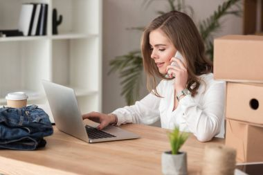 side view of young businesswoman talking on smartphone while working on laptop