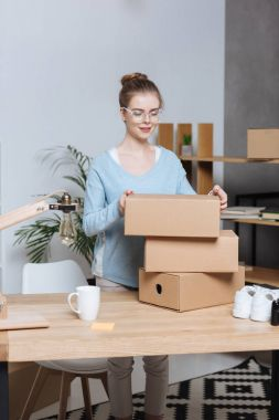 entrepreneur with cardboard boxes working at home office